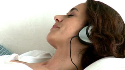 stock-footage-relaxing-hispanic-woman-lying-on-the-sofa-and-listening-to-music-with-headphones-at-home